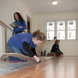 Director of Donor and Volunteer Development installing flooring