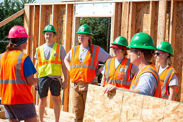 2018 - A group of AmeriCorps members in safety vests and green hard hats listening to their supervisor in a partially-framed house.