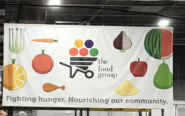 """The Food Group's banner, which includes the logo, as well as illustrations of fruits and vegetables against a white background, and the words """"Fighting hunger. Nourishing our community."""""""