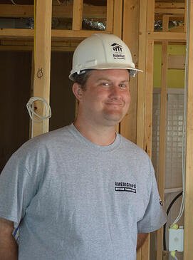 Habitat AmeriCorps Member Mickey Foley leaning against the frame of a house.