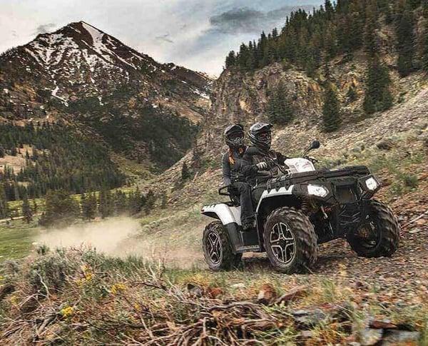 The Sportsman XP1000 ATV driving through the mountains.