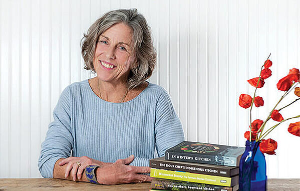 Chef Beth Dooley next to a stack of her books and some red flowers.