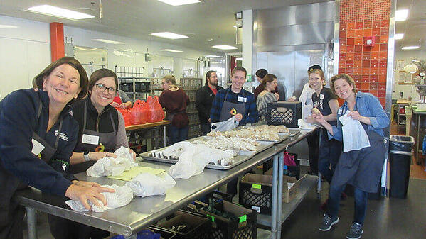 Volunteers preparing food in a kitchen.