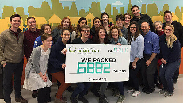 "Volunteers holding a sign with the Second Harvest Heartland logo saying ""We packed 6882 Pounds."""