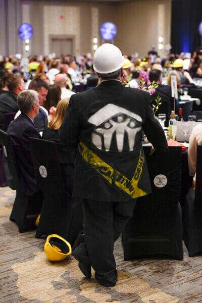 Brian at the 2019 HHBT Gala, wearing a black jacket painted with the Habitat logo and caution tape.