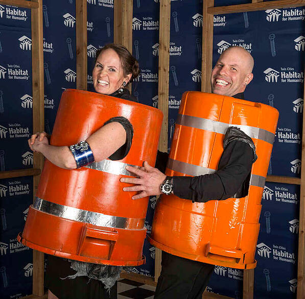 Ashley Rose and her husband at the Hard Hat & Black Tie Gala in 2018, wearing upside-down bins with reflective tape.