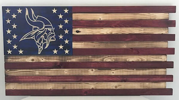 A painted wooden flag with the Vikings logo surrounded by stars.