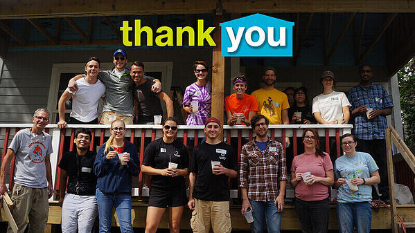 """A group of volunteers standing on a porch. """"Thank you"""" is visible in green and white text above them, with a blue house outlining the """"you."""""""