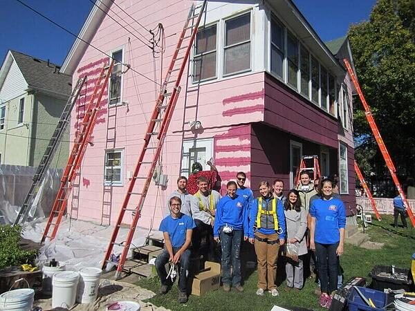 A group of AmeriCorps members in blue shirts and gray shirts, standing outside of a partially-finished house with the pink siding exposed and several ladders leaning against it.