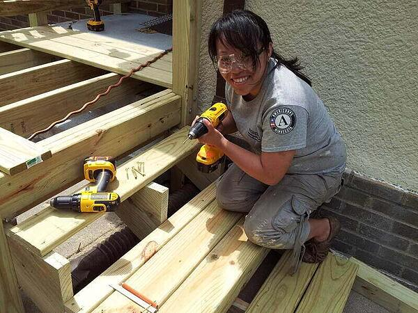 An AmeriCorps member smiling while holding a power drill as she kneels on the stairs she's working on. She's wearing khakis, a gray AmeriCorps shirt, and safety goggles. A power drill sits next to her.