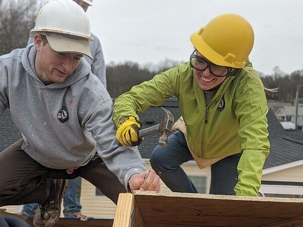 An AmeriCorps member on the right, she's wearing a green jacket with the AmeriCorps logo, a yellow hard hat, safety goggles, and yellow gloves as she uses a hammer on a roof. To her left is another member, he's in a gray AmeriCorps sweatshirt, holding the nail, wearing a white hard hat.