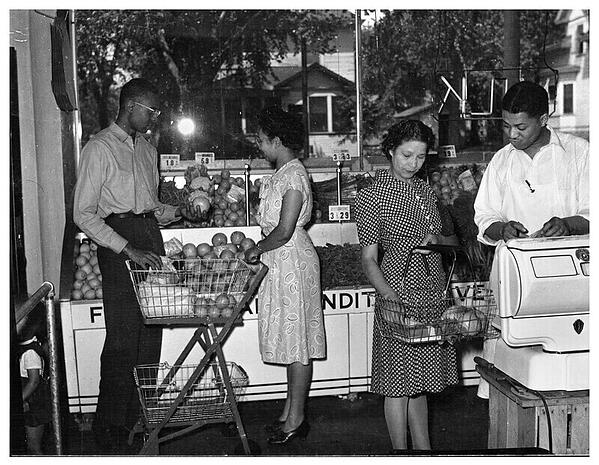 A black and white photo of the Credjafawn co-op, on the left in front of the fruits are a man and woman selecting produce. On the right, an employee shows something to a woman with a basket.