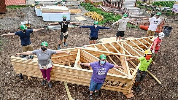 Nine volunteers demonstrating social distancing with open arms as they stand around a series of wood beams forming the triangular roof of a house.
