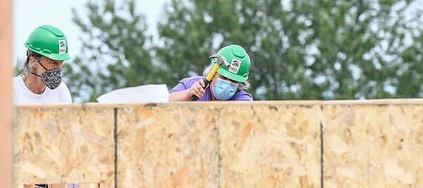 Two volunteers working behind a wall. The one on the right uses a yellow hammer while wearing a purple shirt, green hard hat, and surgical mask. The one on the left watches while wearing a white shirt, green hard hat, and black and white patterned mask.