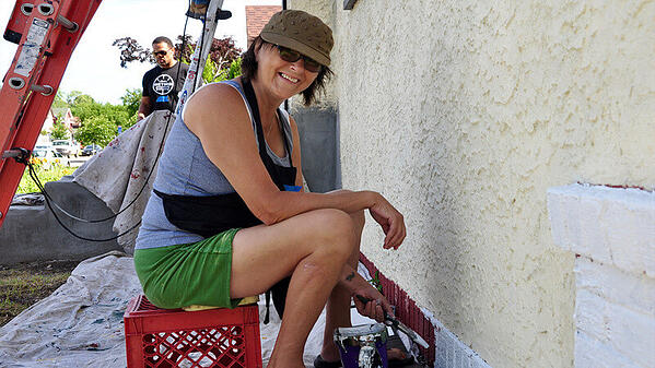 A volunteer in a gray tank top, green shorts, brown hat, and black apron, sitting on a red crate and smiling while she paints the base of a house.