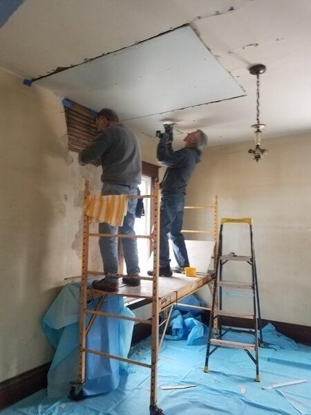 Two volunteers repairing the dining room ceiling.