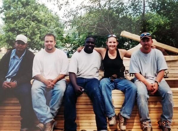 Heather and four men from Sentencing to Service sitting on a pile of wooden beams outside.