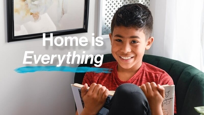 "A young boy reading a book in a chair in his Habitat home, with the text ""Home is Everything"" in white."