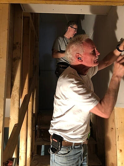 Two Third Act volunteers working on a wall while standing in a stairwell.