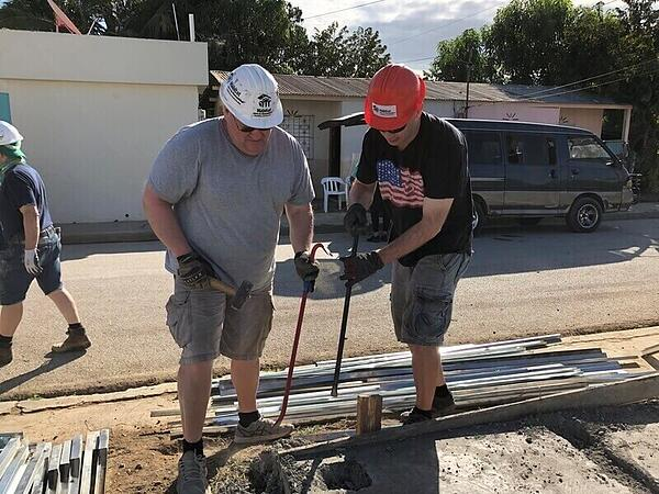 Chad and Joe working on the foundation of a house.