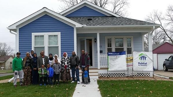 A family standing in front of their new Habitat home.