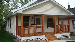 A Habitat home with a wooden front porch.