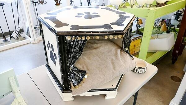 """A hexagonal pet bed/pet """"cave"""" with a pillow, curtains, and small medallions hanging off the opening. It's white with painted paw prints and bones."""