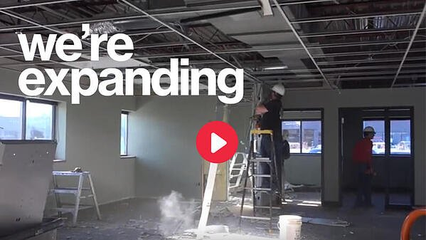 """White text saying """"we're expanding."""" The background is a photo of volunteers doing construction work inside of the New Brighton Store. A red """"play"""" button is in the middle of the image."""