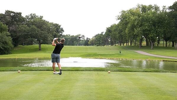 A man in a black shirt and gray shorts swinging a golf club in front of a pond on a golf course, on a cloudy day.