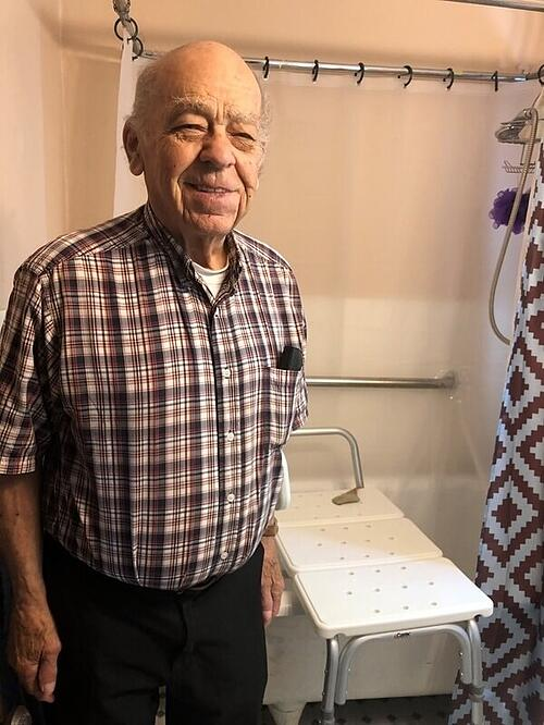 Homeowner James Sass in front of his new modified bathtub, complete with hand rail, detachable shower head, and a bathtub seat. He's smiling and wearing a plaid shirt.