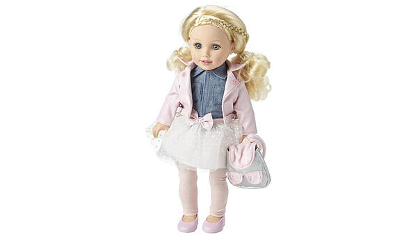A blond doll with pigtails, wearing a denim shirt, a white skirt with a pink bow, a pink jacket with leggings and pink shoes, as well as a gray and pink backpack.