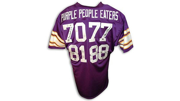 "A purple Vikings jersey that says ""Purple People Eaters"" on the back, with the numbers 70, 77, 81, and 88 below it. Each number is signed by the player who wears that number, listed below."