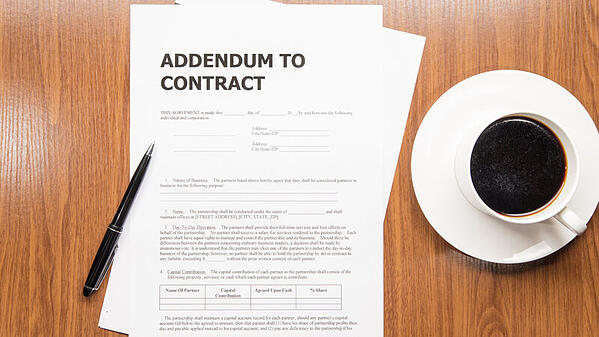 "On a wooden background, a couple sheets of white paper with the words ""ADDENDUM TO CONTRACT"" at the top and an unreadable form below. A black pen sits atop the paper. A cup of black coffee on a saucer sits to the right."