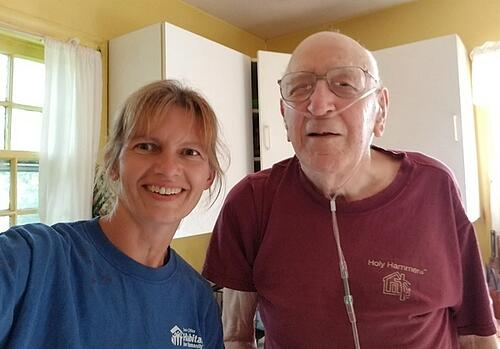 Lynda and Ken smiling and standing in Ken's kitchen. Lynda's wearing a blue TC Habitat shirt and Ken is wearing a red Holy Hammers shirt.