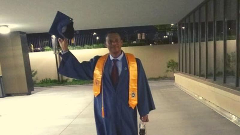 Endireas waving his graduation cap outside of Saint Paul College.