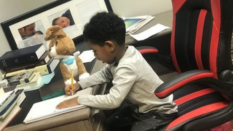 Jacob doing homework in a black and red desk chair at a desk, with a stuffed dog.