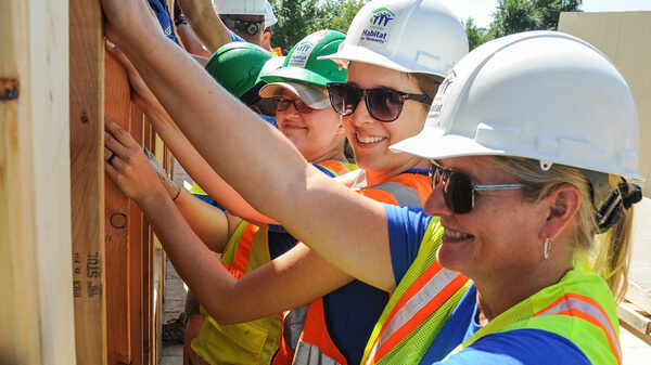 A row of volunteers holding up a wall and smiling, all wearing hard hats, safety vests, and the two in front are wearing sunglasses.