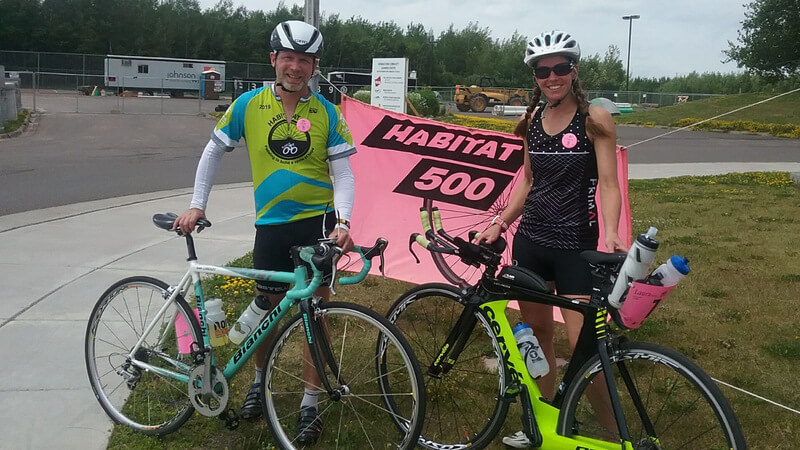 Mike and Laura on the corner of a street with their bikes, in front of a pink Habitat 500 sign.
