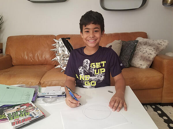 Ayden drawing a picture on a table in his living room, his backpack on the couch behind him.