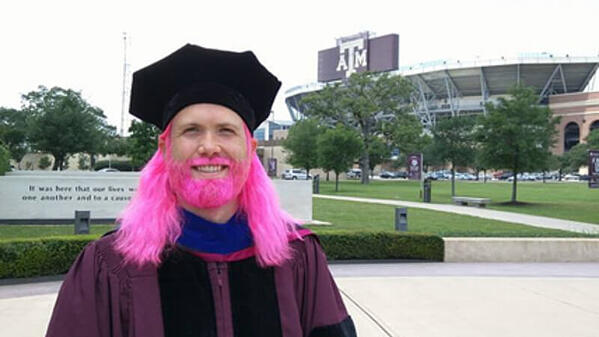 Jimmy, with bright pink hair and beard, in his graduation cap and gown outside of the Texas A&M stadium.