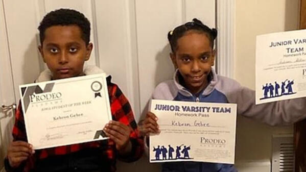Samuel's two kids holding three different award certificates.