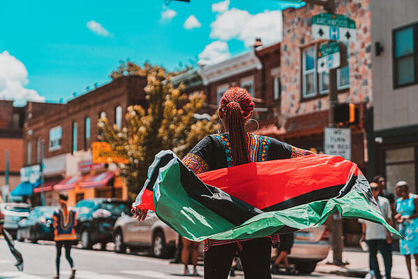 A woman wears the pan-Afridan flag as a shawl in the street during a Juneteenth celebration.