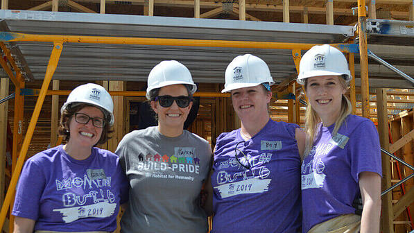 Four volunteers wearing Women Build and Build Pride shirts in front of an in-progress house.