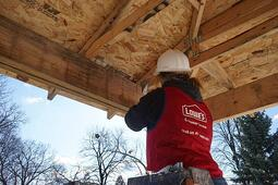 A volunteer in a Lowe's vest, working on a roof.