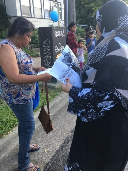 Two women reading informational pages about the Census.