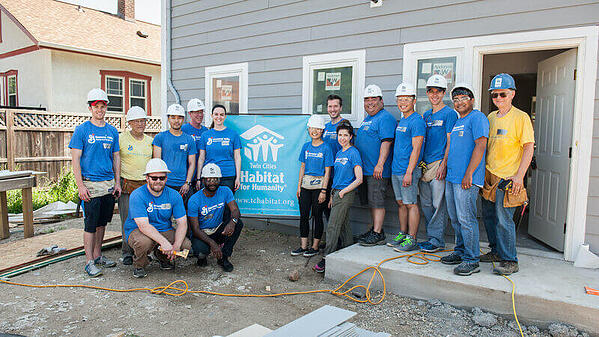 A group of General Mills volunteers outside of an in-progress house, with a Twin Cities Habitat sign behind them.