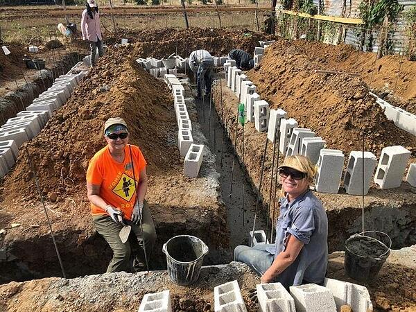 Volunteers working on the foundation of a home.