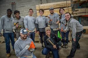 Several AmeriCorps members posing with various tools.
