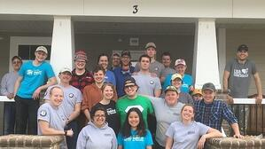 An AmeriCorps cohort on their service trip, posing on the porch of a house.