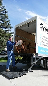 A man loading a side table into the ReStore donations truck.